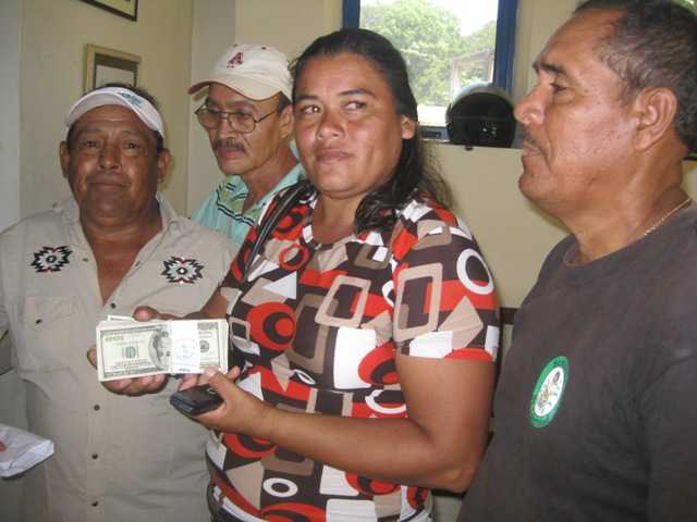 Rosa, Ojochal's community leader, delivers NCF money for the electricity project to the Mayor's office.